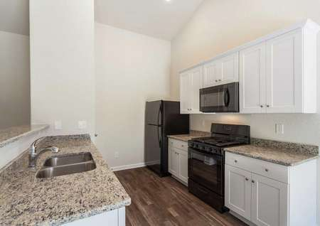 Alexander kitchen with black appliances, granite counters, and white cabinets