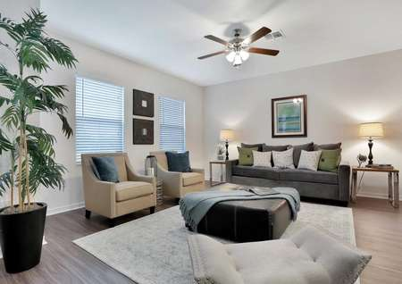 Fully furnished living room in the Pine Key floor plan. The room has tile flooring, white walls and a ceiling fan