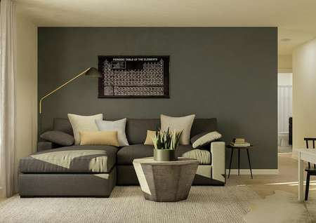Rendering of the loft space with a   window, dark gray couch and coffee table. To the side there is a small white   children's table.