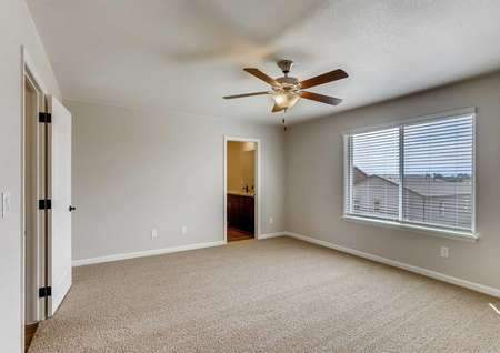 San Juan bedroom with large window with blinds, ceiling fan fixture, and private bathroom