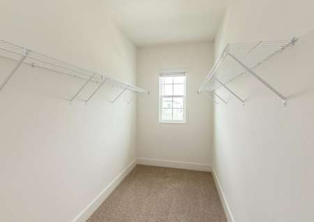 Large walk-in closet with plenty of storage space and a window overlooking the front of the home.