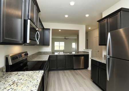 Upgraded kitchen of the Driftwood home by LGI Homes with granite counters, dark wood cabinetry, recessed lighting, pale plank flooring, stainless appliances.