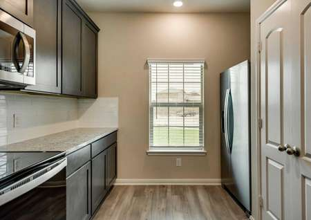 Kitchen with stainless steel appliances and front yard views.