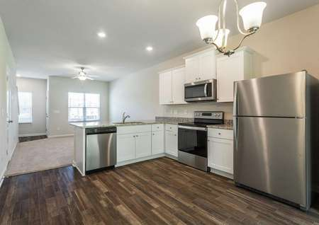 Chestnut kitchen with stainless appliances and white cabinets.