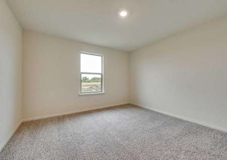 Bedroom in the Oakmont with carpet flooring,white trim baseboards, recessed lighting and exterior window