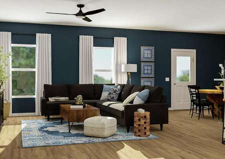 Rendering of the   open floor plan showcasing the living room with ceiling fan and two windows,   black couch and wood coffee table, with the dining room and kitchen visible   in the back