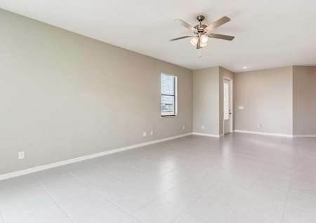 The spacious living room in the Santa Maria model home. Tile flooring, a ceiling fan, white baseboards and tan walls