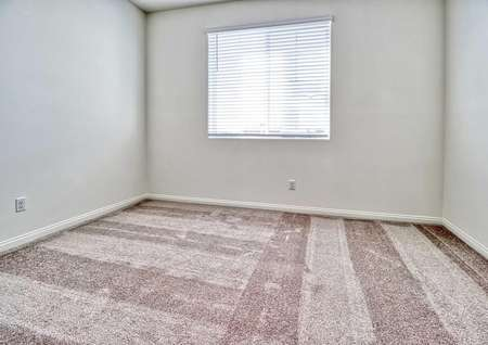 A spare bedroom in the Rosebud floor plan with light brown carpet, white baseboards and walls with a window on one of them.