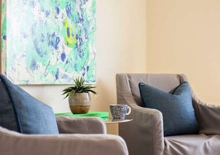 Driftwood family room completed with gray chair with blue pillow, small house plants in a vase, and blue and yellow wall art hanging up