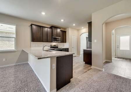 Maple kitchen with recessed lighting, granite finish countertops, and custom brown wooden cabinets
