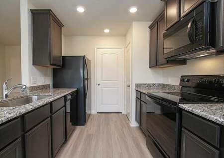 Trinity kitchen with ceramic flooring, dark brown cabinetry, and black appliances
