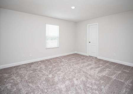 Carpeted spare room in the Kiawah floor plan with a closed closet door and a single hung window covered by blinds.