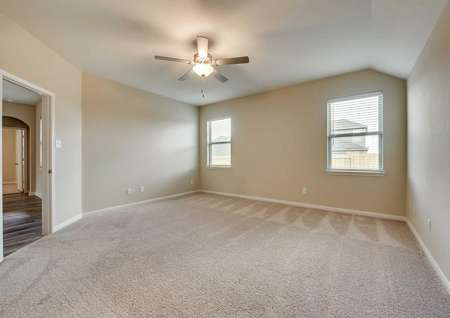 Two single hung windows and a ceiling fan in a carpeted spare bedroom of the Houghton floor plan.