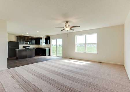Nicollet great room completed with soft brown carpet, overhead ceiling fan, and brown kitchen cabinets
