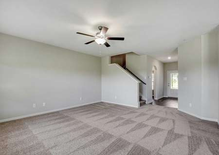 Shelby family room with overhead ceiling fan, stairs to second level, and brown carpet throughout