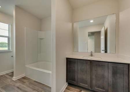 The secondary bath has wood style flooring, brown cabinetry and plenty of space.