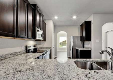 Fannin completed kitchen with light color granite, under mounted sink, and browned cabinetry
