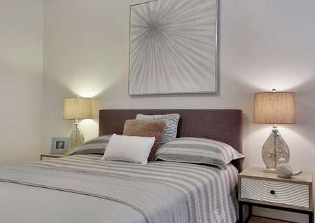 Bed with gray linens, side tables with lamps and a decorative wall hanging