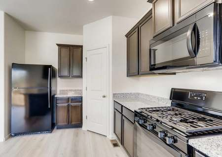 Yale kitchen with black appliances, gas stove/oven, and light color wood style floor