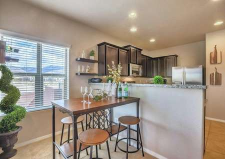 Sierra model home completed with furnishings including small dining table with pull-up bar stools, spiraling house plant, and shelves with decor on them