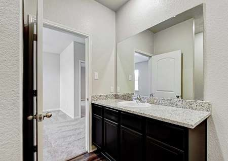 Fannin bathroom finished with granite counters, white sink, and brown cabinetry