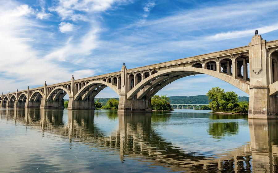Columbia-Wrightsville Bridge in Pennsylvania with double arched bridge over large waterway with blue skies