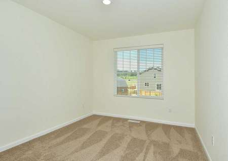 The Northwest Oak second bedroom shown carpeted with a single window on the back wall.
