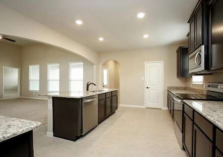 Spacious kitchen with tile floor, dark brown cabinets, light granite, stainless appliances, antique bronze fixtures, recessed lighting, archway between kitchen and living room, view of living room with three windows and ceiling fan and door to bedroom.