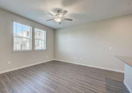 The Empire floor plan living room has two windows, a ceiling fan with a light and vinyl wood flooring.