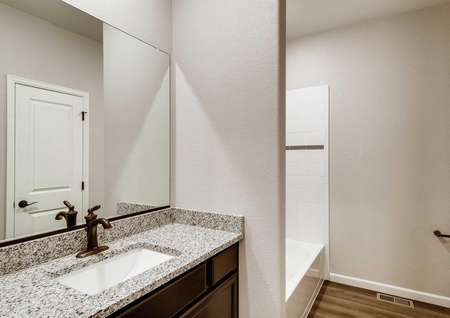 A bathroom in the Pike floor plan withbrown cabinets and granite countertops.
