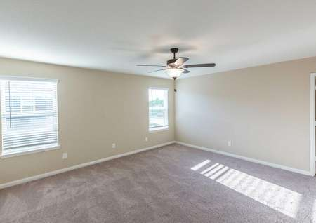 Willow completed home with large windows with blinds, tan carpeting, and beige colored walls