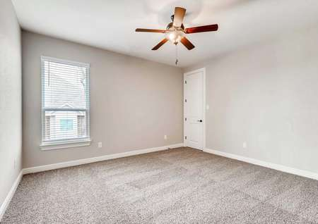Timberline bedroom with light brown carpet, tan walls with white trim, and brown ceiling fan