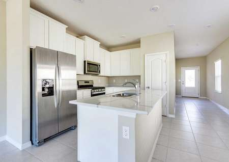 The kitchen in the Alafia floor plan to the left and a view of the hallway and front door to the right.