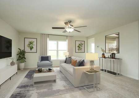 Staged living room with carpet and throw rug, window to backyard, drapes, ceiling fan, sofa, armchair, coffee table, end table with lamp, mirror on back wall with table.
