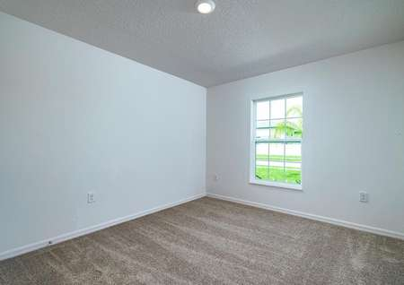 Carpeted spare bedroom with a window overlooking the front yard.