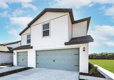 Angle view of townhome with a two-car garage and a side entry.