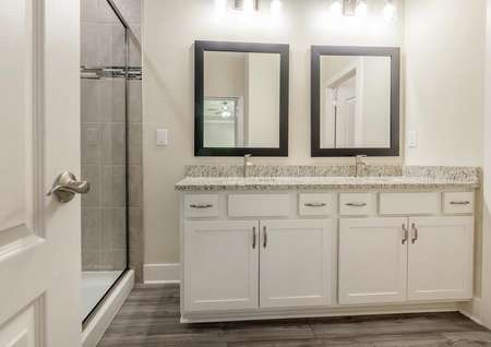 Master bathroom featuring double sinks and a spacious shower.