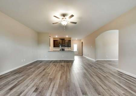 Houghton floor plan's spacious living area with vinyl wood flooring and a ceiling fan with a light fixture.