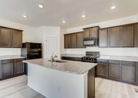 Harvard kitchen with dark brown cabinetry, granite countertops, and island with sink and barstool counter
