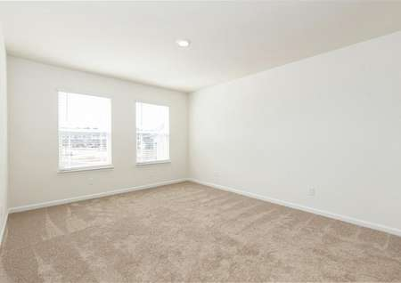 Spacious master bedroom with two windows, carpet, recessed light.