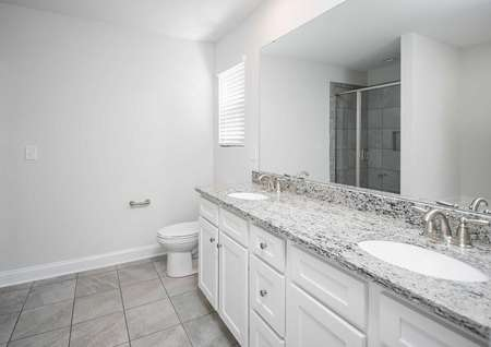 A bathroom in the Kiawah floor plan with tile flooring, double sink vanities, granite countertops and white cabinets.