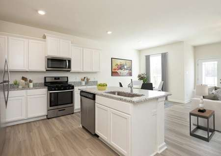 Open-concept kitchen, dining and living room with lots of natural light featuring pale plank flooring, white cabinets, stainless appliances, gray granite counters, recessed lights.