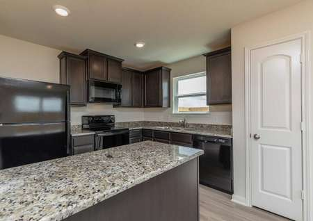 Blanco kitchen with speckled granite countertop, black appliances, and canned lighting