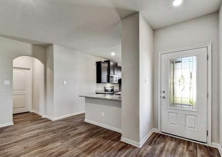 Jasper entryway with white glass door, gray wall with white trim, and brown tile flooring