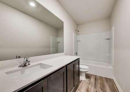The secondary bathroom has luxury vinyl plank flooring, a shower/tub combo and great vanity.