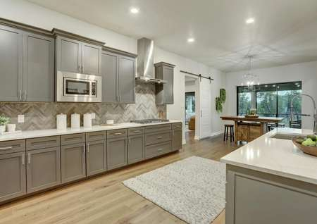 Staged kitchen with gray cabinetry and white countertops.