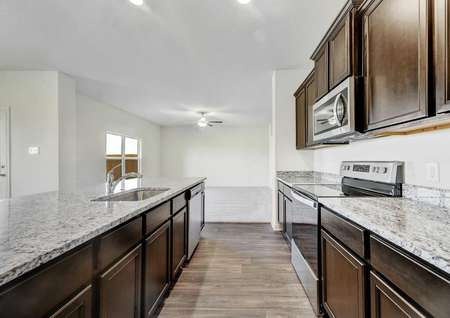 Rio finished kitchen with brown cabinets, hardwood floors, and light colored granite countertops