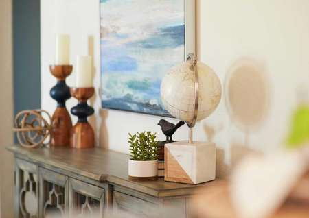 Living room decor with white globe, candles and brown dresser.