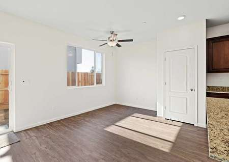 The living room has gorgeous wood-style floors, a ceiling fan and great natural light.