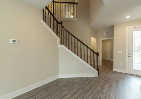 Foyer of two-story home with a beautiful stairway.